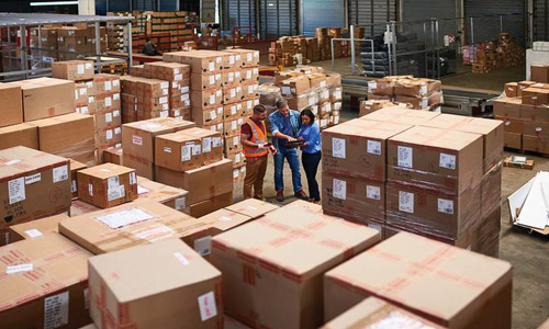 People working together in a warehouse full of boxes